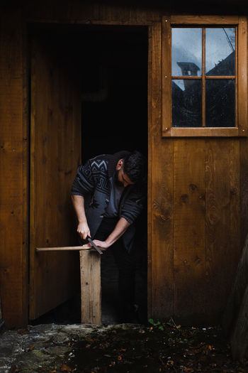 Man working on wood at door of house