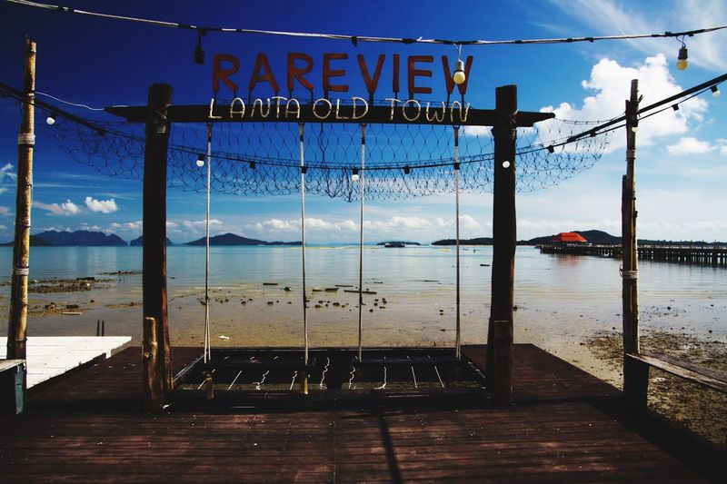 View from wood pier with a swing on islands of andaman sea at Ko Lanta old town during low tide Clouds And Sky Swing Thailand Ko Lanta Wood - Material Sea Andaman Water Sky Sea Communication Text Nature Railing No People Cloud - Sky Outdoors Sign Western Script Pier Blue