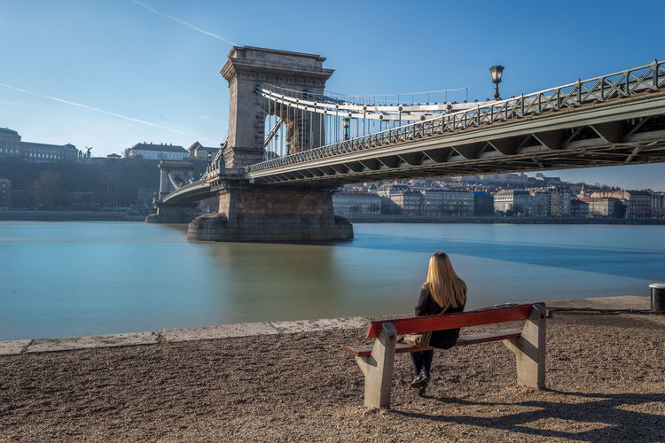 Woman sitting on bench looking at chain bridge over river danube in city