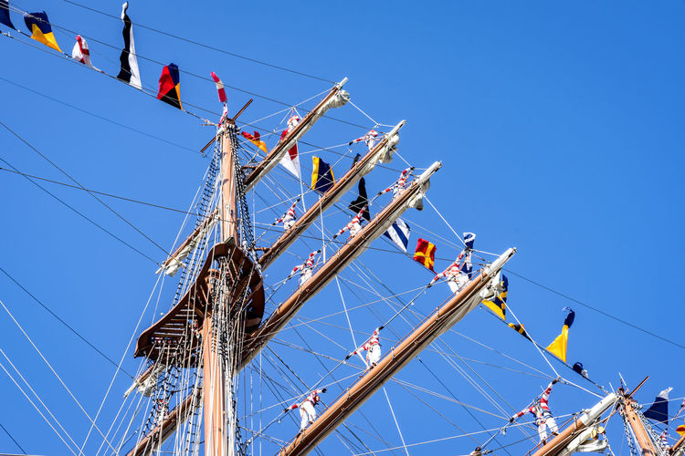 Low angle view of flags on mast against clear blue sky