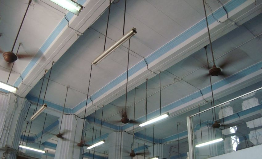 Low Angle View Of Illuminated Lighting Equipments Hanging At Ceiling