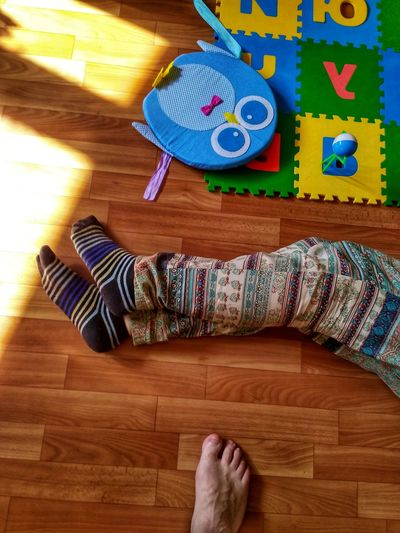 Low section of person relaxing on wooden floor