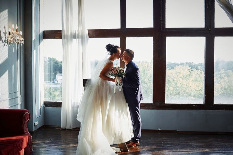 Side view of bride and bridegroom kissing against window