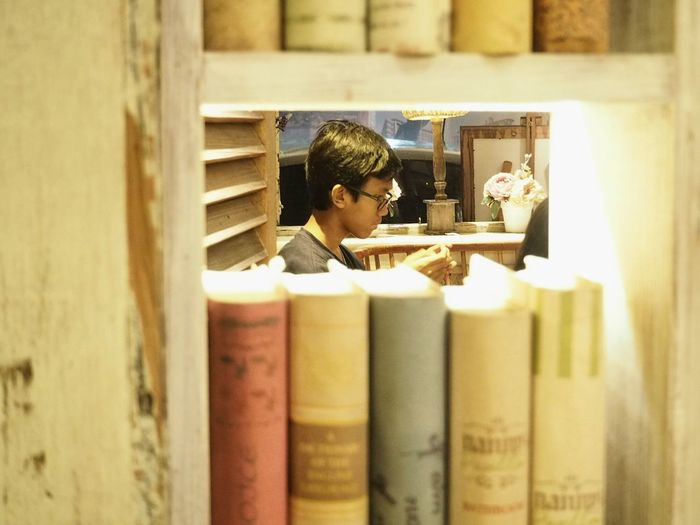 Boy seen from bookshelf in library