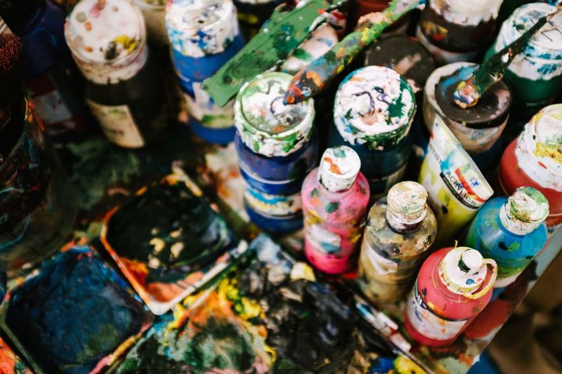 High Angle View Of Colorful Paint Cans At Workshop