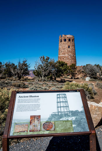 Desert View Tower at Grand Canyon Arizona Brick Wall Desert View Tower Grand Canyon Architecture Blue Building Building Exterior Built Structure Clear Sky Day Detail History Information Sign Land No People Outdoors Plant Singe Sky Sunlight The Past Tree
