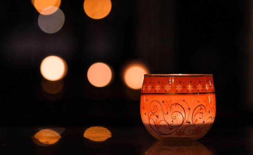 Close-Up Of Illuminated Tea Light Candle Against Defocused Lights