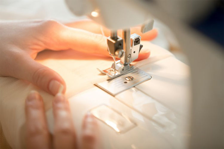 Cropped hands of woman sewing cloth at table