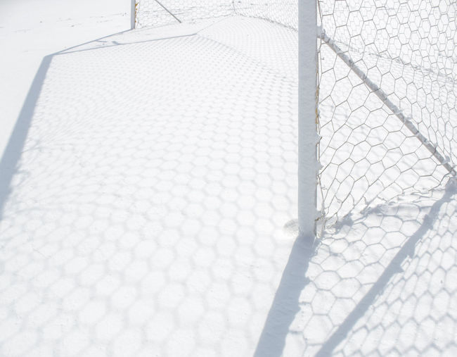 Close-up of metal fence with snow