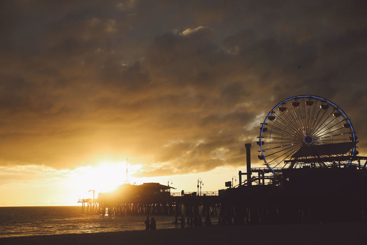 Silhouette Santa Monica Pier Against Cloudy Sky During Sunset