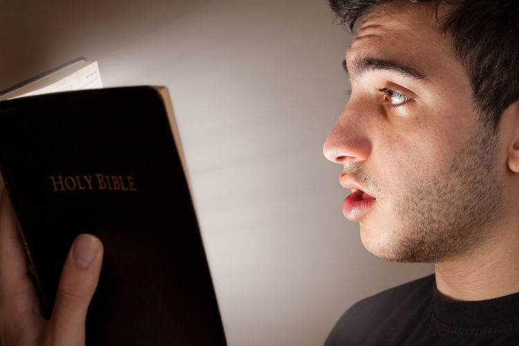 Young Man Reading Bible in Amazement People person Christian Christianity Religion Spirituality Faith Born-again Holy Bible King James Bible Amazed Shocked Revelation Truth Eye Opening Question Questioning Answers Q&A