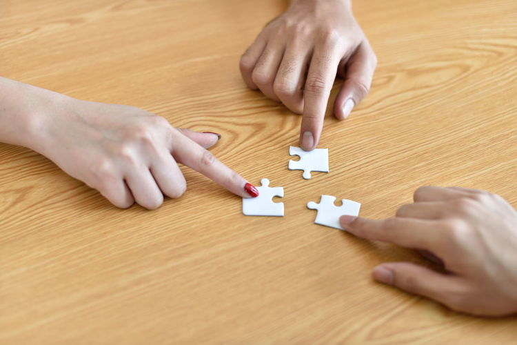 Cropped hands of people holding jigsaw pieces on table