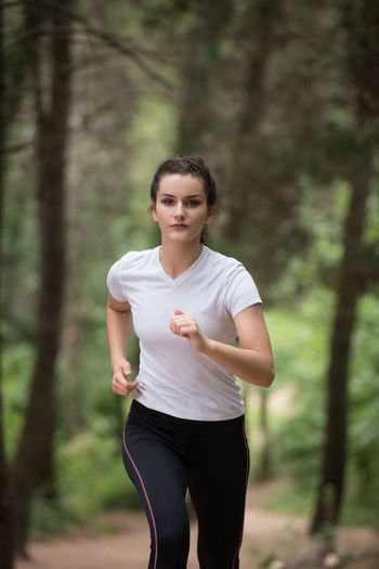 Full length of young woman running in forest