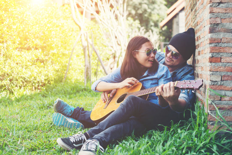 Happy couple looking at each other while playing guitar while sitting on grassy field against brick wall