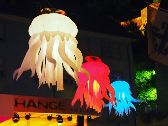 Low angle view of illuminated decorations sign at night