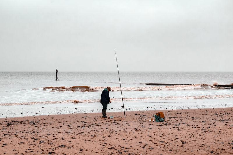 Men fishing at beach against sky