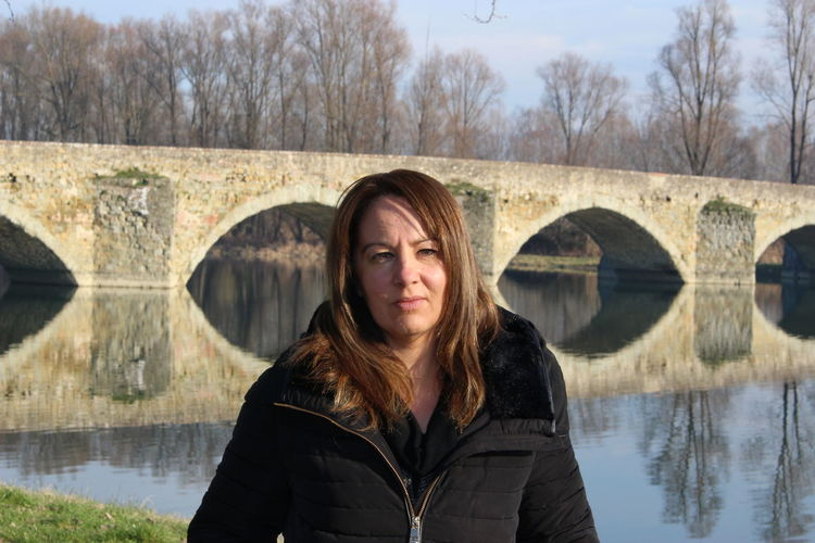 Portrait of woman standing by lake against bridge