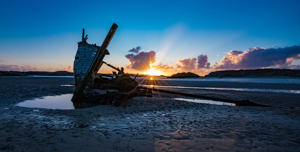 Abandoned boat at beach against sky during sunset