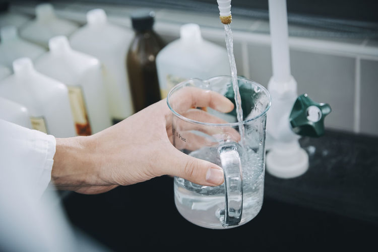 Close-up of hand pouring water in glass