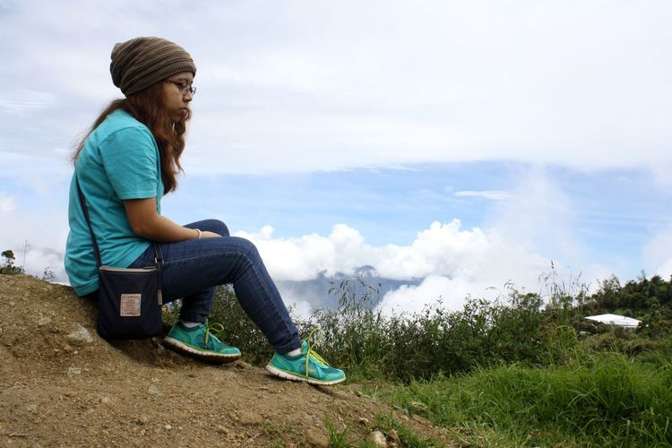 Side View Of Sad Woman Sitting On Mountain Against Sky