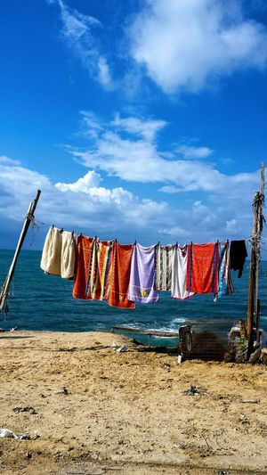 Clothes drying on clothesline against sky