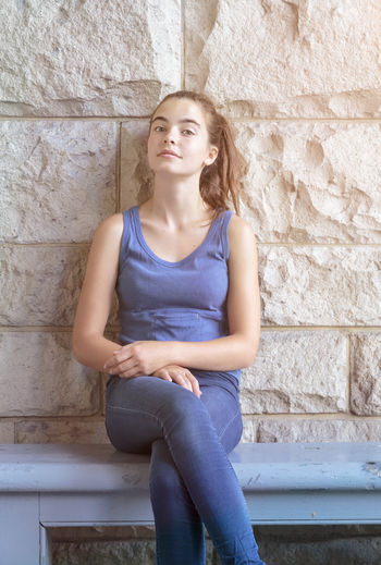 Portrait of woman sitting on bench by wall