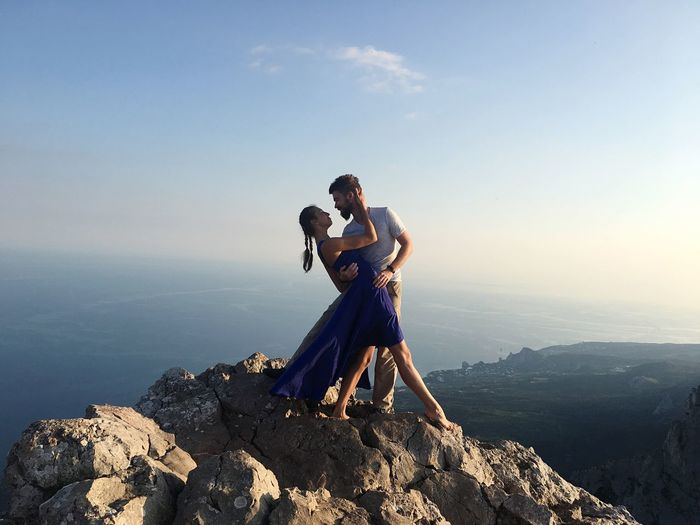 Romantic couple standing on mountain against sky