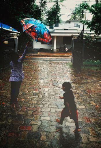 Full length of friends on street during rainy season