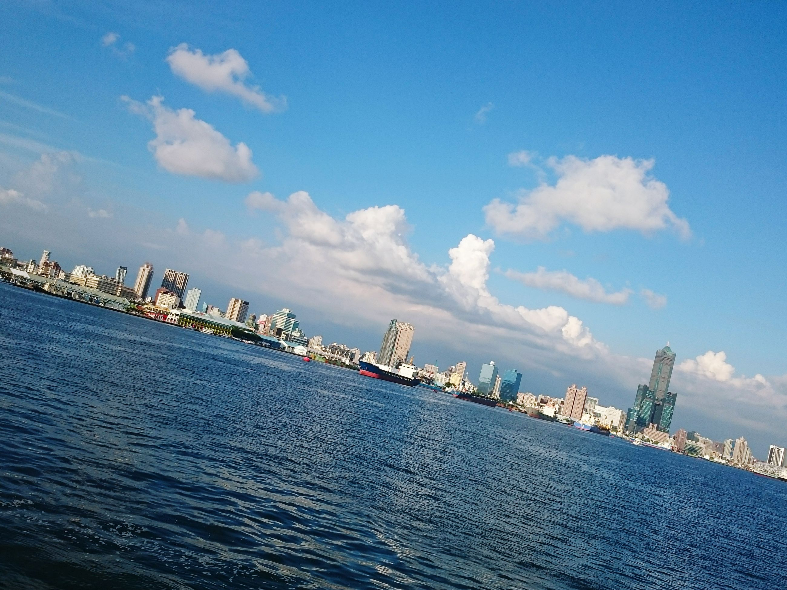 water, sea, blue, architecture, building exterior, built structure, sky, waterfront, cloud - sky, cloud, city, rippled, nautical vessel, day, outdoors, harbor, nature, scenics, cityscape, tranquility