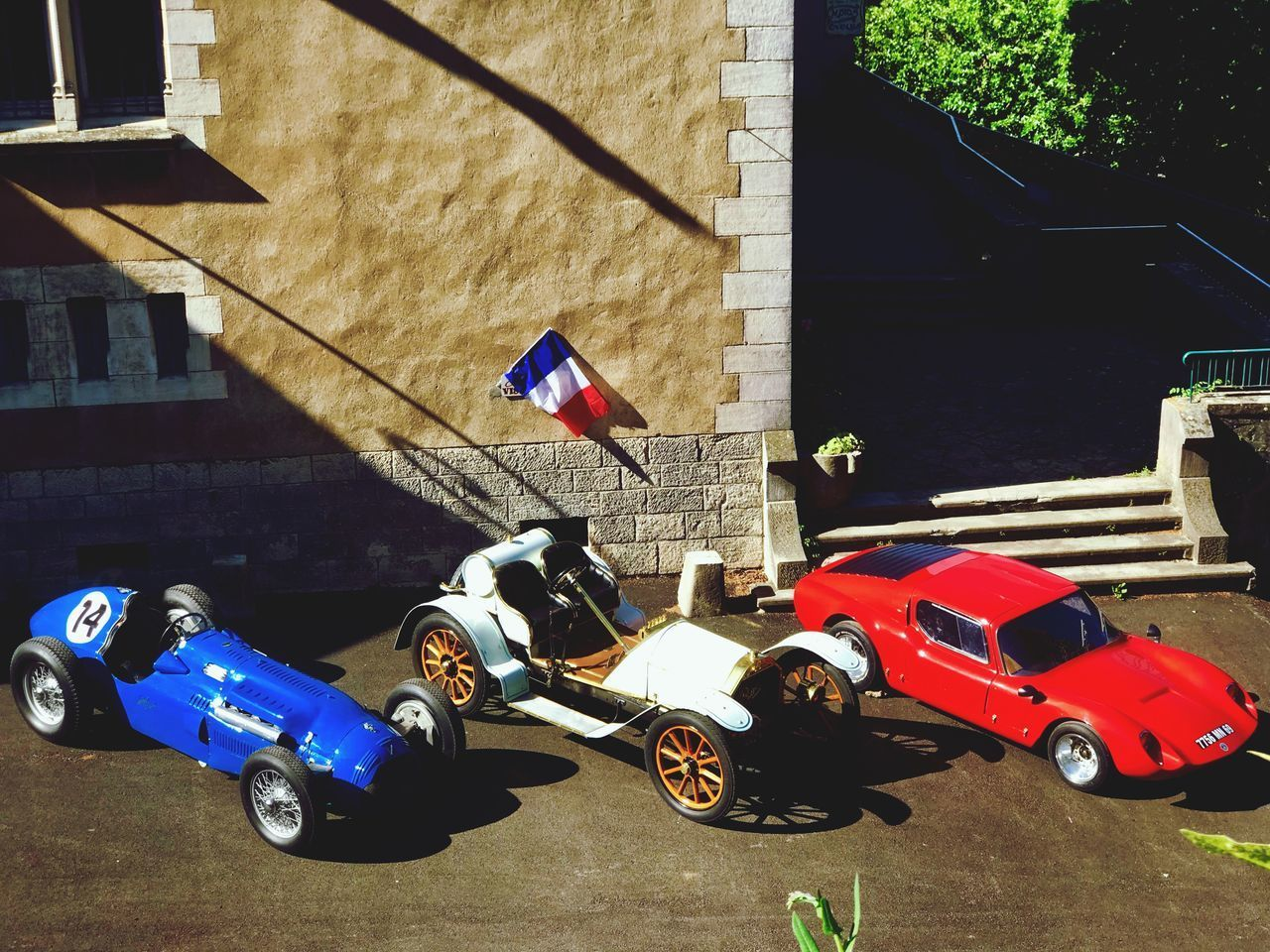 car, transportation, motor vehicle, mode of transportation, building exterior, architecture, built structure, city, land vehicle, day, building, high angle view, street, sunlight, toy, no people, outdoors, nature, toy car, scooter, garage