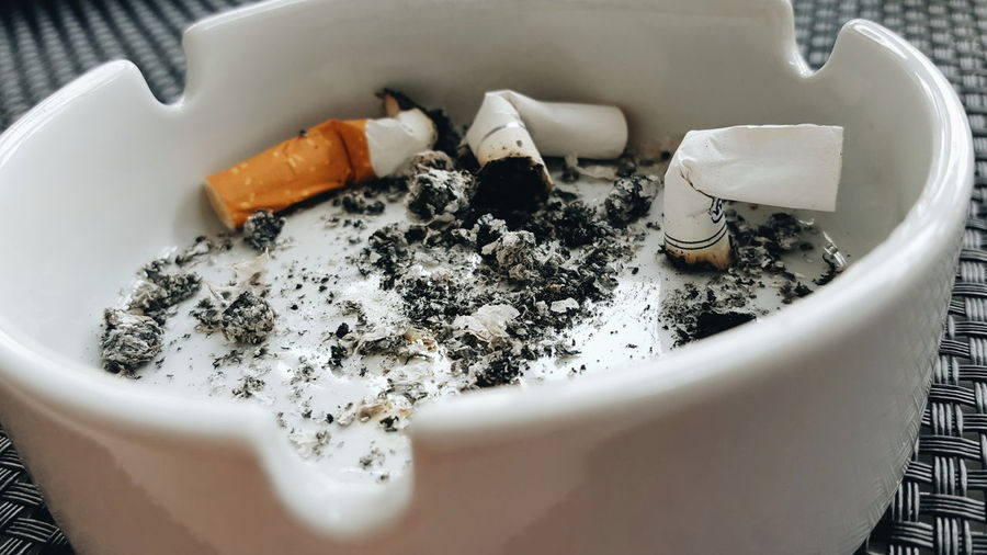 High angle view of cigarette butts in ashtray on table