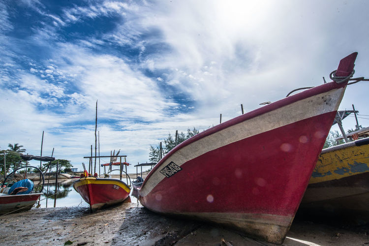 Boats moored on lakeshore against cloudy sky