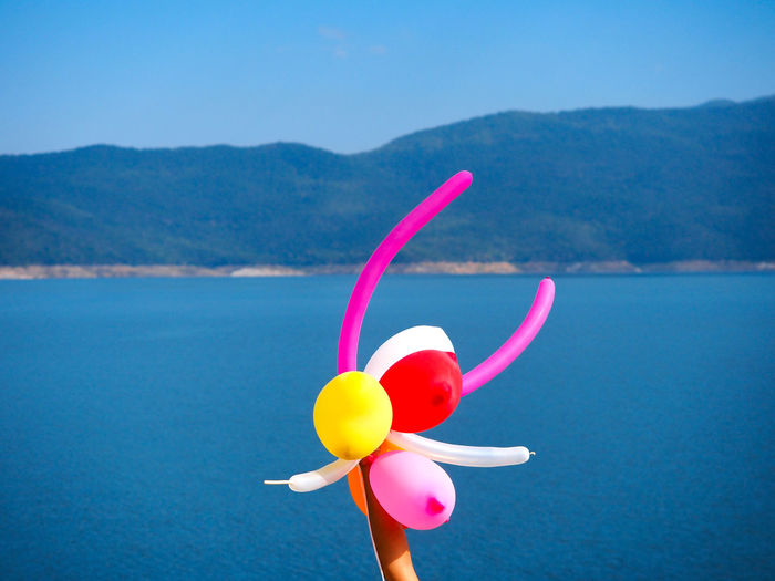 Woman hand holding colorful balloons in center on blue water and sky background for happiness or vacation concept. Center Freedom Happiness Holiday Balloon Ballooning Festival Beauty In Nature Blue Sky Day Festival Focus On Foreground Hand Holding Lifestyles Mountain Nature Outdoors Pink Color Pinwheel Toy Rainbow Scenics - Nature Sunlight Toy Vacation Water