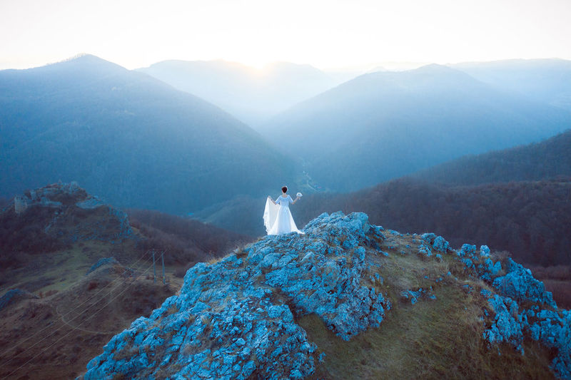 Rear view of bride standing on mountain against sky