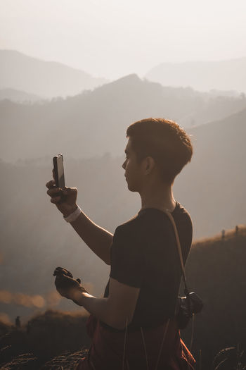 Man photographing on mobile phone against sky