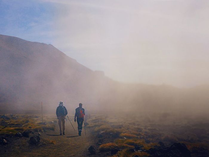 Rear view of men walking on road against mountain and sky