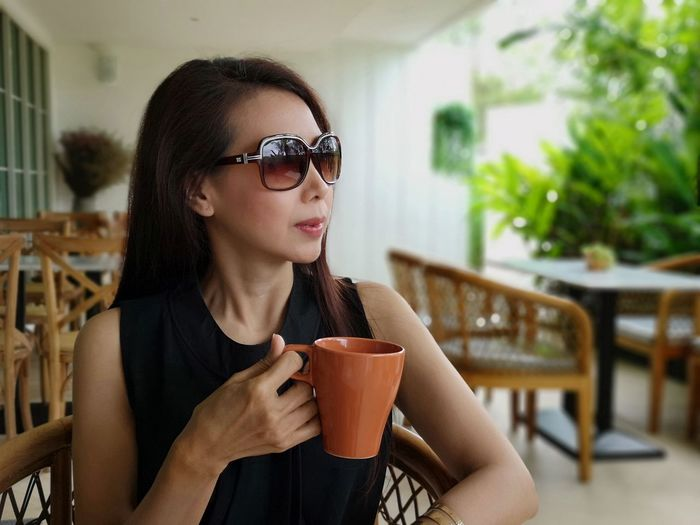 Mature woman with coffee cup sitting in cafe