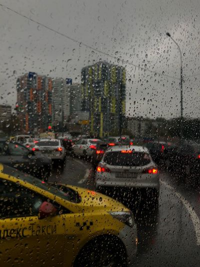 City seen through wet glass window during rainy season