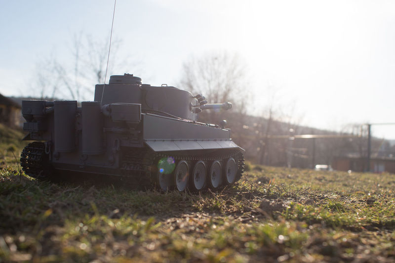 mini tank toy driving in sunset Land Field Day Nature Sky Transportation No People Land Vehicle Outdoors Grass Military Tank Motion Landscape Clear Sky Station Engine Weapon Old Vintage Camouflage Front Combat Toy Tank Cannon