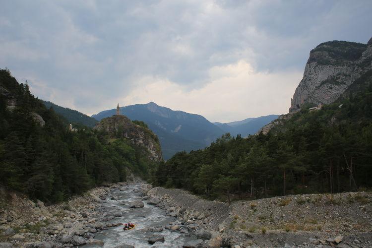 People Canoeing In Stream Along Landscape