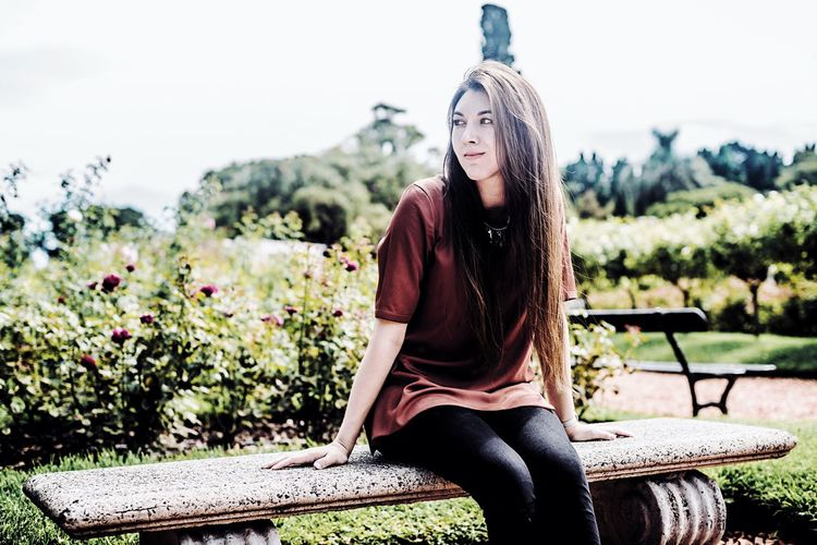 Young woman looking away while sitting on seat at park