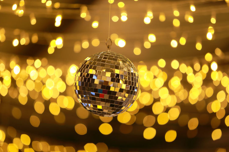Disco ball with color blonde bokeh background. Bright Celebration Decoration Disco Ball Event Indoors  Light Music Night Nightclub Reflection Shiny Sphere