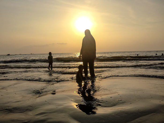 Beach Beauty In Nature Horizon Horizon Over Water Land Leisure Activity Lifestyles Men Nature Outdoors Real People Reflection Scenics - Nature Sea Silhouette Sky Sun Sunset Togetherness Water