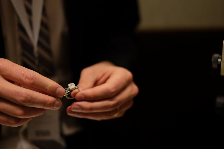 Midsection of bridegroom holding wedding ring