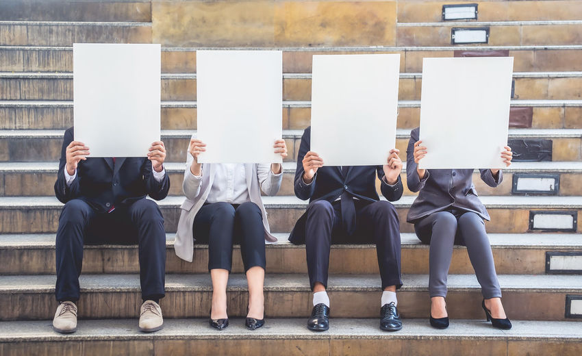 Business people holding billboards while sitting on steps