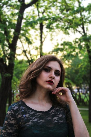 Portrait of thoughtful young woman against trees