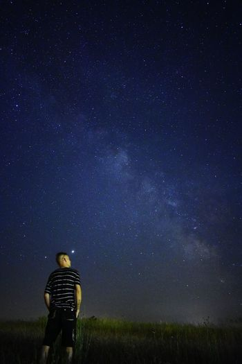 Rear view of man on field against sky at night