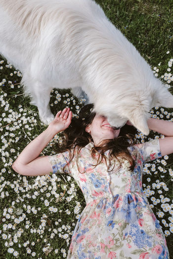 Midsection of woman with dog in field