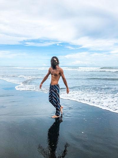 Full length of shirtless man at beach against sky