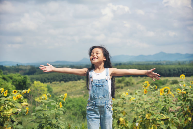 Happy girl with arms outstretched standing on land